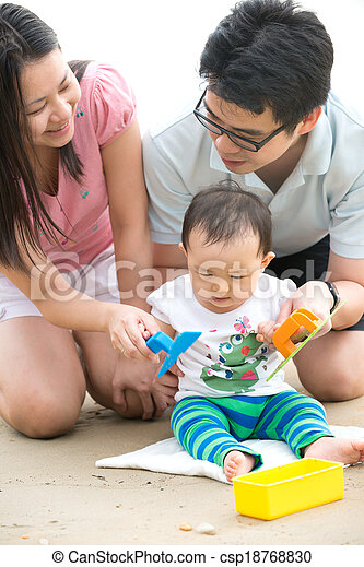 asian baby playing sand on the beach with father and mother - csp18768830