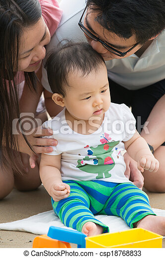 asian baby playing sand on the beach with father and mother - csp18768833