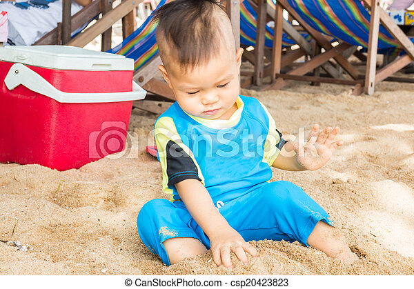 Asian boy playing sand on the beach - csp20423823