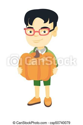 asian boy standing with a big orange pumpkin cheerful asian boy