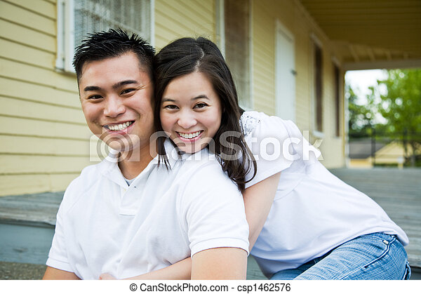 Asian couple in front of their house - csp1462576