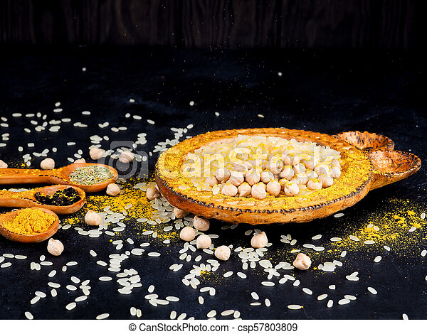 Asian cuisine, spices, rice, chickpeas and turmeric on a plate - csp57803809