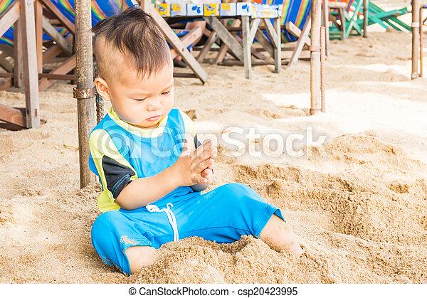 Asian cute boy playing sand on the beach - csp20423995