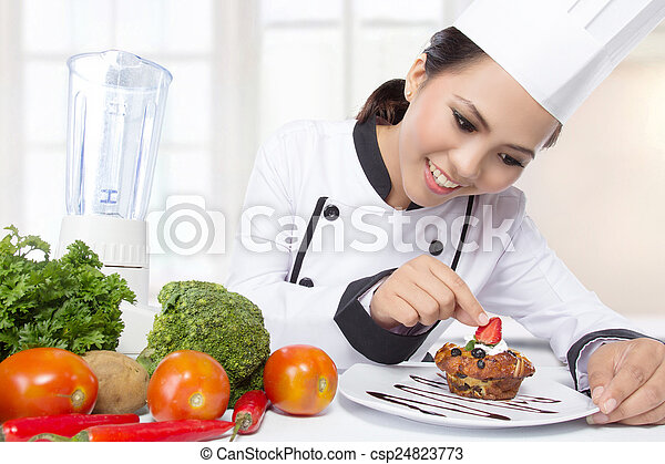 asian female chef garnishing - csp24823773