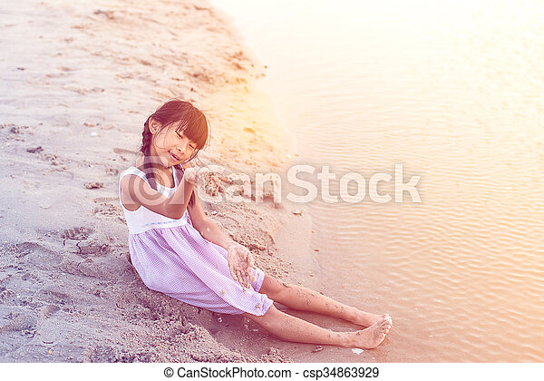 Asian girl playing sand on the beach - csp34863929