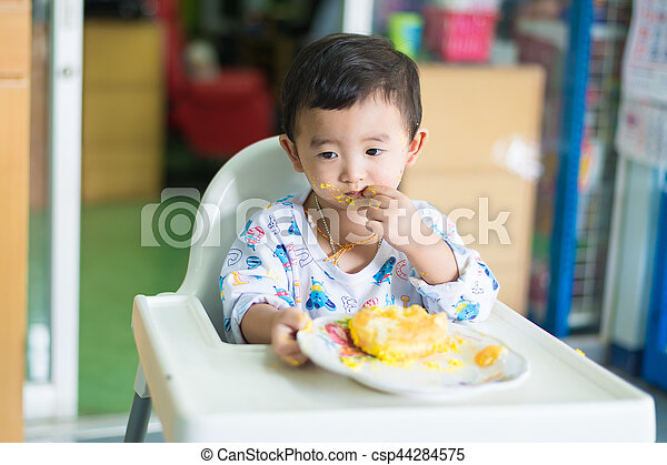 Asian kid eating birthday cake with cream on face Asian kid