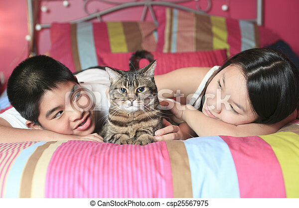 Asian kid lay on his bedroom with cat - csp25567975