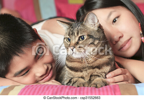 Asian kid lay on his bedroom with cat - csp31552663