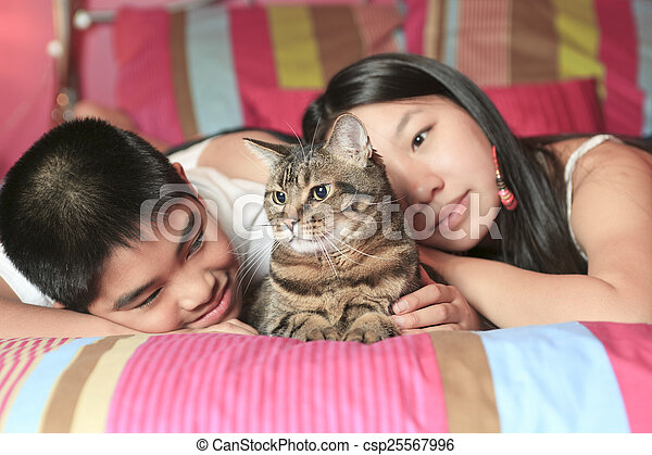 Asian kid lay on his bedroom with cat - csp25567996