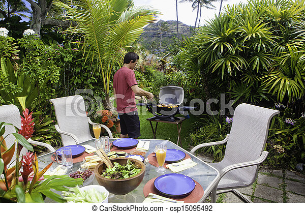 asian man cooking on a barbecue - csp15095492