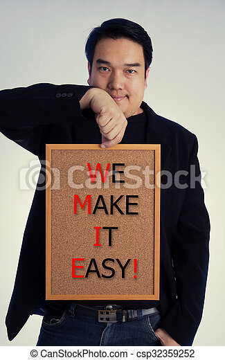 Asian man in black suit with WE MAKE IT EASY! message on white board - csp32359252
