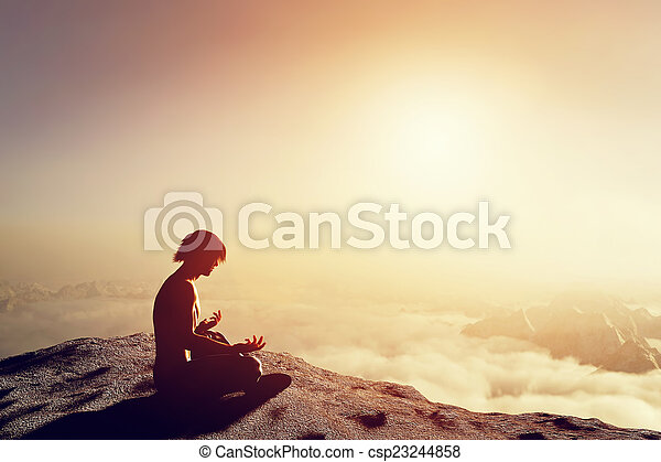 Asian man meditates in yoga position in high mountains above clouds at sunset - csp23244858