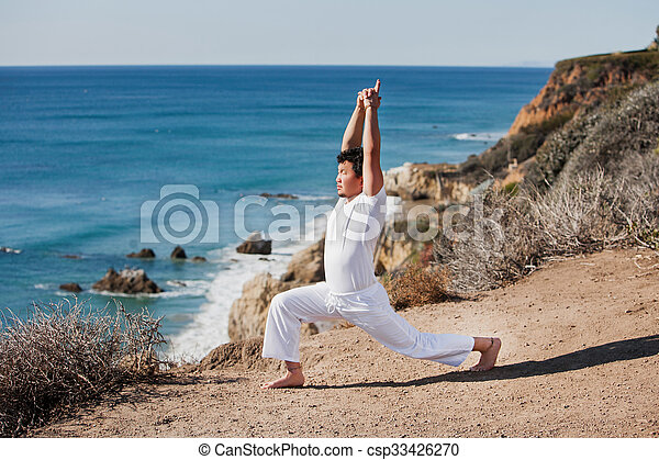 Asian man meditates in yoga position on high mountains above blue sky.  - csp33426270