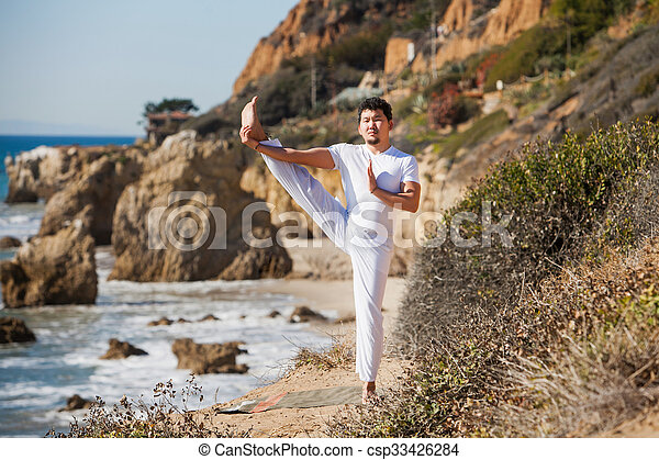 Asian man meditates in yoga position on high mountains above blue sky.  - csp33426284