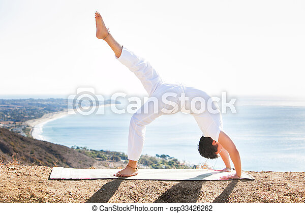 Asian man meditates in yoga position on high mountains above blue sky.  - csp33426262