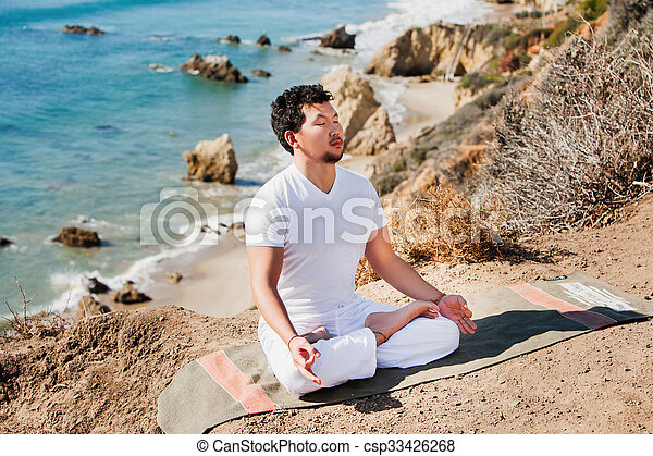 Asian man meditates in yoga position on high mountains above blue sky.  - csp33426268