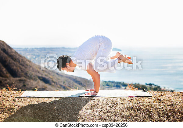 Asian man meditates in yoga position on high mountains above blue sky.  - csp33426256