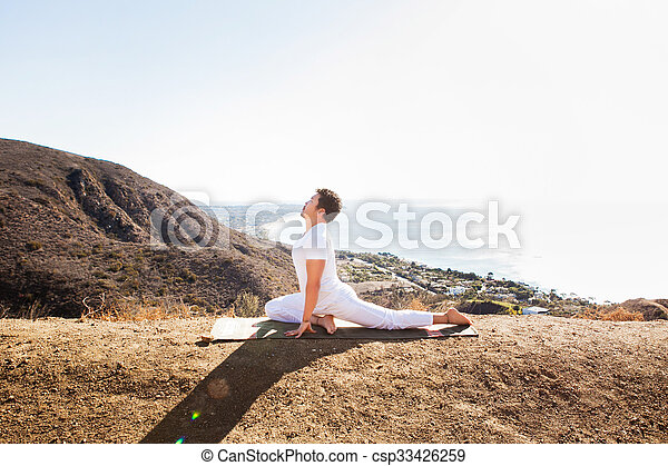 Asian man meditates in yoga position on high mountains above blue sky.  - csp33426259