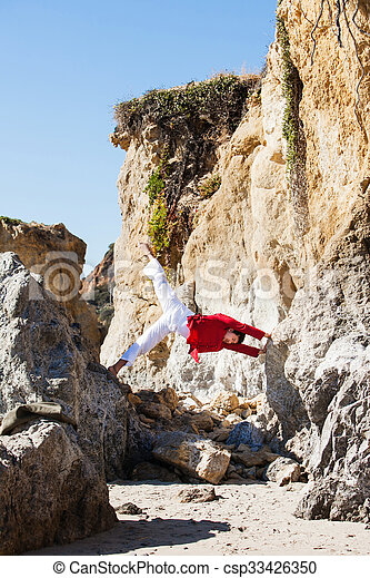 Asian man meditates in yoga position on high mountains above blue sky.  - csp33426350