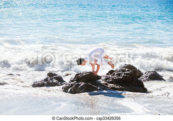 Asian man meditates in yoga position on high mountains above blue sky.  - csp33426356