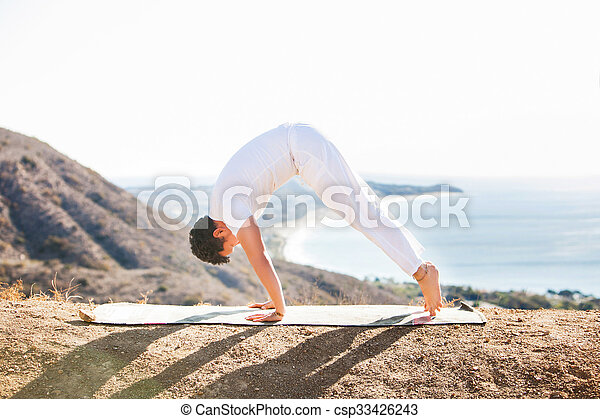 Asian man meditates in yoga position on high mountains above blue sky.  - csp33426243