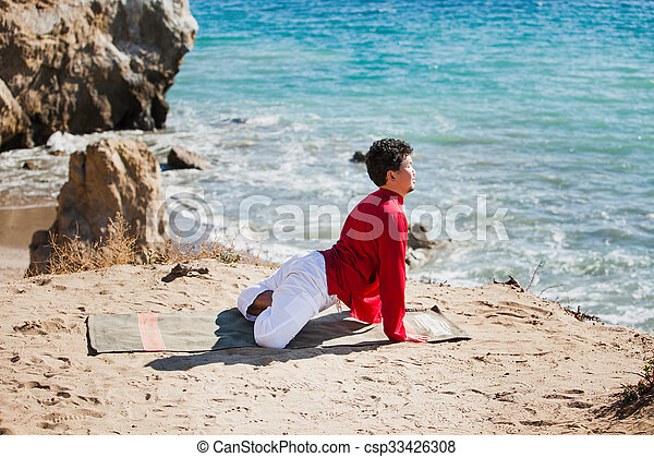 Asian man meditates in yoga position on high mountains above blue sky.  - csp33426308