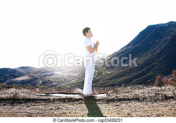 Asian man meditates in yoga position on high mountains above blue sky.  - csp33426231