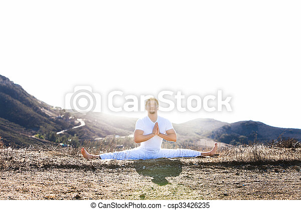 Asian man meditates in yoga position on high mountains above blue sky.  - csp33426235