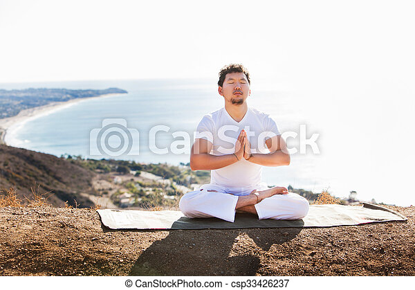 Asian man meditates in yoga position on high mountains above blue sky.  - csp33426237