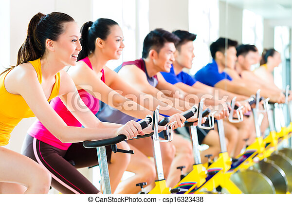 Asian people spinning bike training at fitness gym - csp16323438