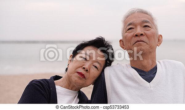 Asian senior couple enjoy their life time together at the sea - csp53733453