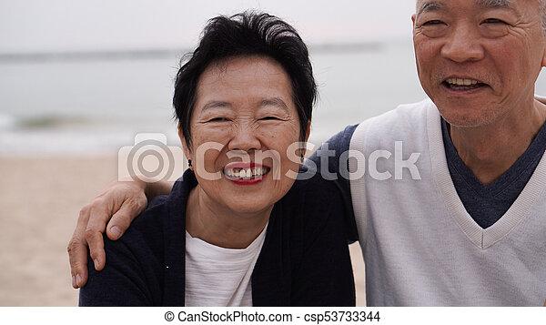 Asian senior couple enjoy their life time together at the sea - csp53733344
