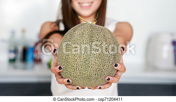 Asian Thai Teenager Woman Holding Cantaloupe Melon On His Hand Showing And Raising Up To You With Blur Modern Kitchen Pobierz to zdjęcie cantaloupe in hand the farm teraz. can stock photo