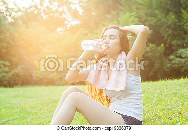 asian woman are drinking and sitting on the lawn. - csp19336379