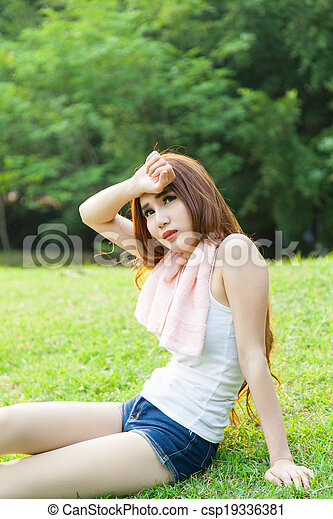 asian woman are tired sitting on the lawn. - csp19336381