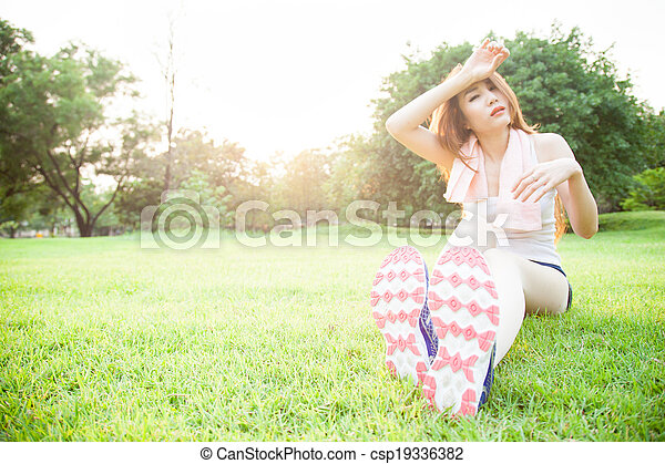 asian woman are tired sitting on the lawn. - csp19336382