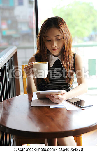 Asian woman drinking coffee with tablet - csp48054270
