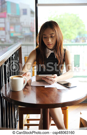 Asian woman drinking coffee with tablet - csp48063160