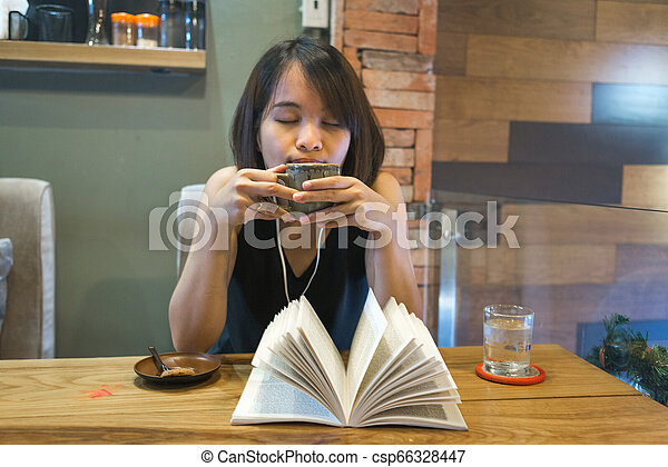 Asian woman enjoy free time with book, coffee and music - csp66328447