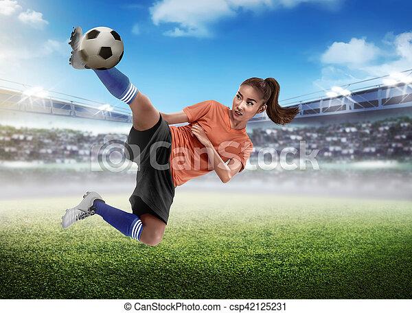 Asian woman football player kick ball - csp42125231