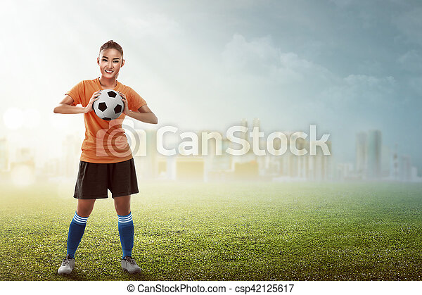 Asian woman holding soccer ball - csp42125617