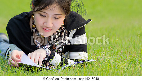Asian woman reading notebook on the - csp14216948
