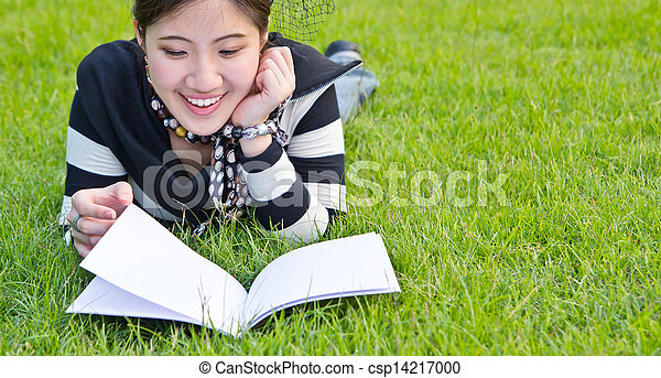 Asian woman reading notebook on the - csp14217000