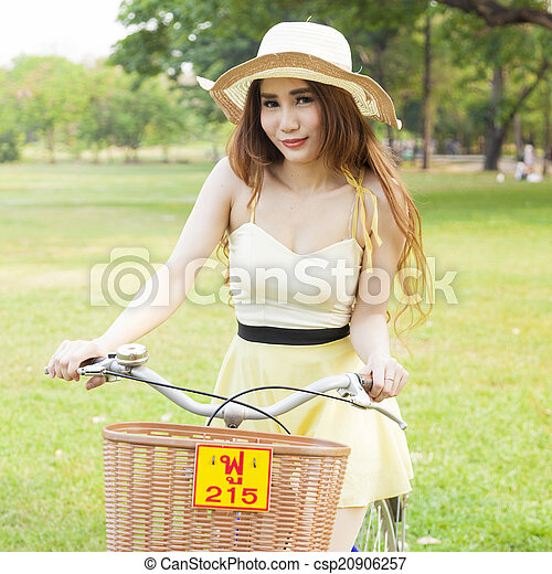 Asian woman riding a bicycle - csp20906257