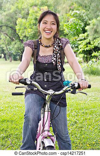 Asian woman riding bicycle - csp14217251