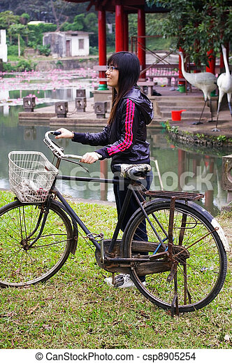 Asian woman riding bicycle with smile - csp8905254
