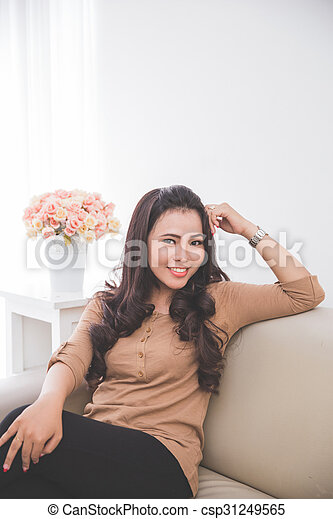 asian woman sitting on the couch - csp31249565