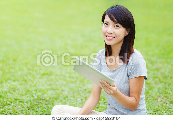 Asian woman sitting on the lawn with tablet - csp15928184