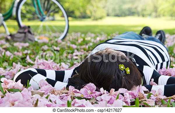 Asian woman sleeping on the grass - csp14217627