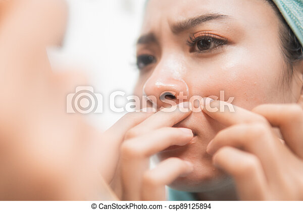 asian woman squeezing pimple on the cheek to the mirror - csp89125894